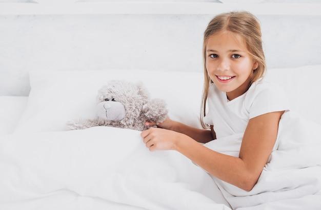 Menina sorridente de alto ângulo, ficar na cama com seu ursinho de pelúcia