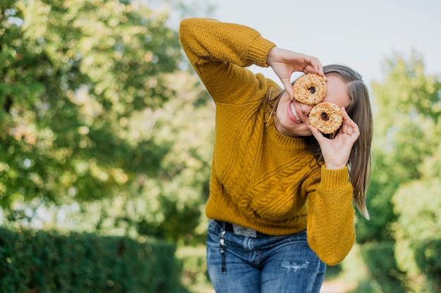 Menina sorridente de baixo ângulo com donuts ao ar livre