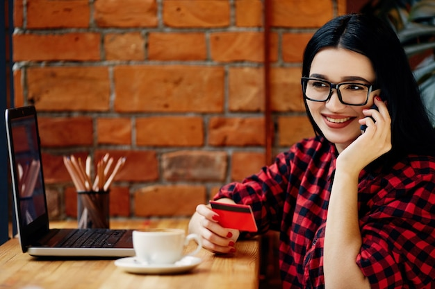 Menina sorridente de cabelo preto, usando óculos, sentado no café com laptop, telefone celular, cartão de crédito e uma xícara de café, conceito freelance, compras online, vestindo camisa vermelha.