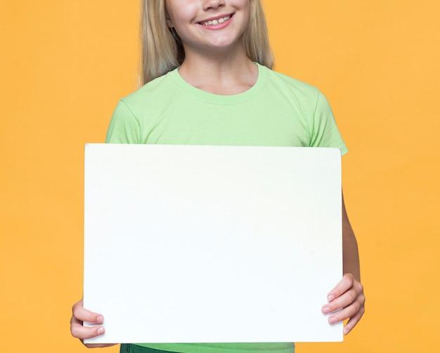 Menina sorridente de close-up, segurando a folha de papel em branco