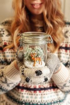 Menina sorridente de close-up, segurando o frasco com veado