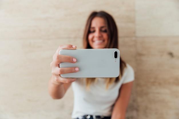 Menina sorridente de close-up tomando uma selfie