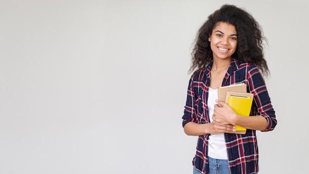 Menina sorridente de cópia-espaço com pilha de livros