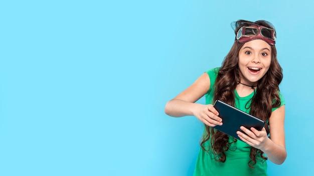 Menina sorridente de cópia-espaço jogando no tablet
