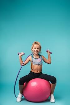 Menina sorridente de esportes fazendo exercícios com diferentes equipamentos esportivos isolados sobre uma parede azul