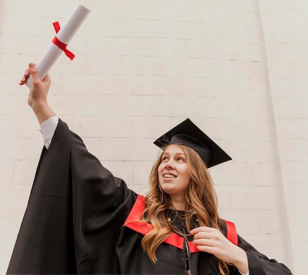 Menina sorridente de retrato com diploma