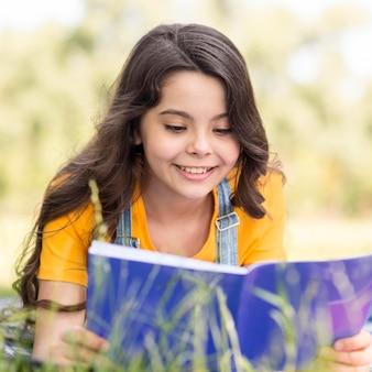 Menina sorridente de retrato lendo