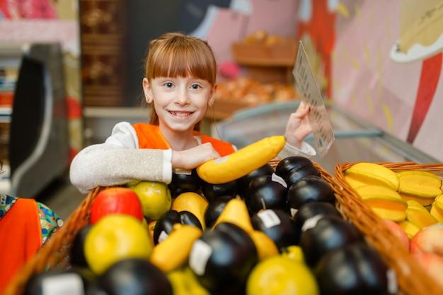 Menina sorridente de uniforme brincando de vendedora