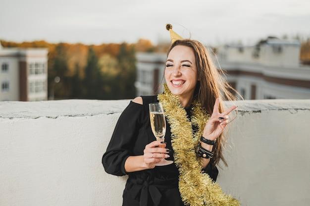 Menina sorridente de vestido preto, segurando uma taça de champanhe na festa no terraço