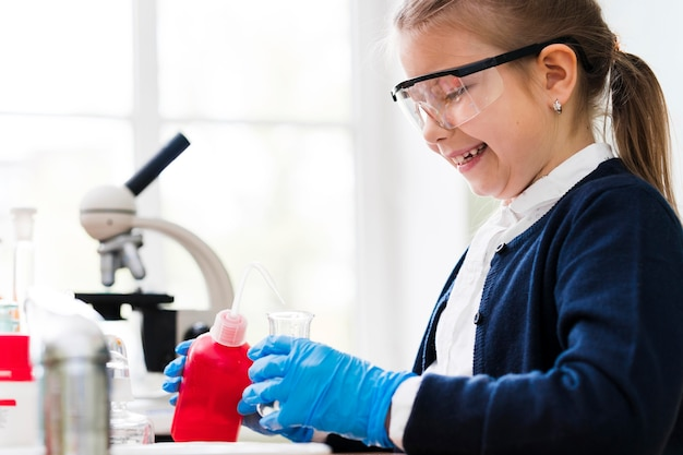 Menina sorridente de vista lateral com óculos de proteção