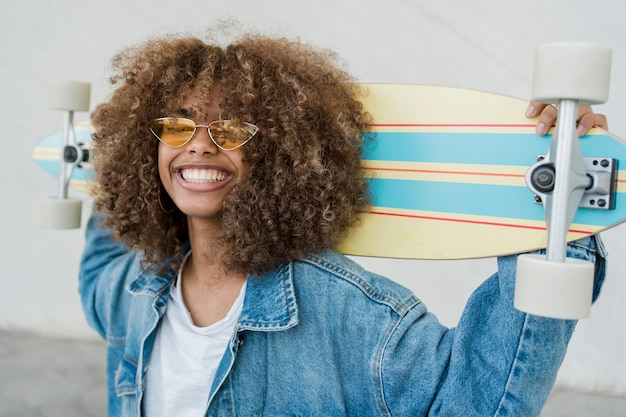 Menina sorridente de vista lateral com skate