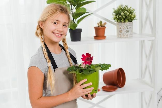 Menina sorridente de vista lateral com vaso de flores