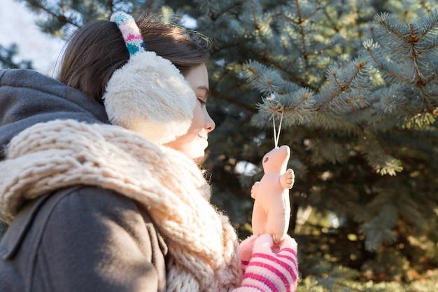 Menina sorridente decora árvore de natal com brinquedo, hora dourada