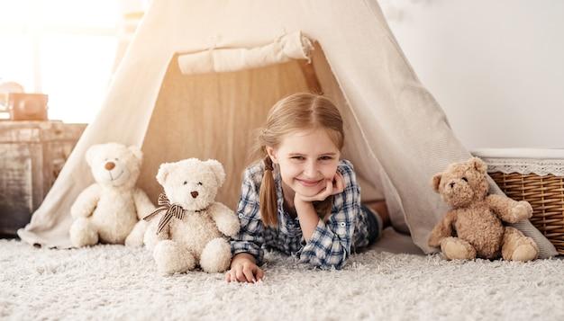 Menina sorridente deitada na cabana com ursinhos de pelúcia