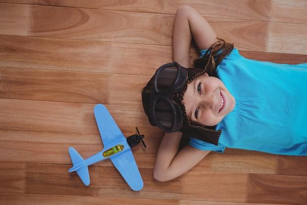 Menina sorridente deitada no chão usando óculos e chapéu de aviador