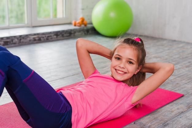 Menina sorridente, deitado de costas fazendo exercícios de alongamento no chão