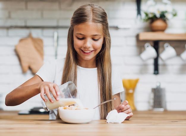 Menina sorridente, derramando leite em uma tigela de cereais