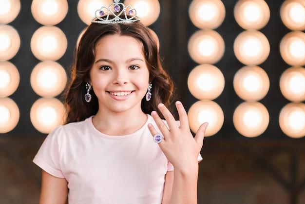 Menina sorridente, desgastar, coroa, mostrando, dela, anel dedo, contra, fase, luz