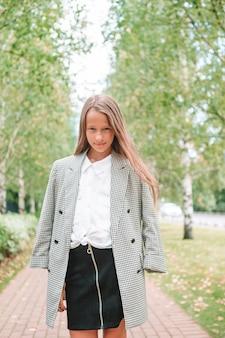Menina sorridente e fofa posando na frente da escola
