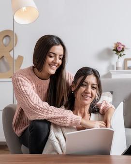 Menina sorridente e mãe lendo