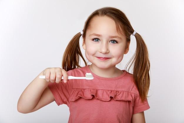 Menina sorridente e satisfeita enquanto escova os dentes