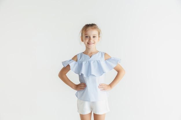Menina sorridente elegante posando com roupas casuais, isoladas no estúdio branco