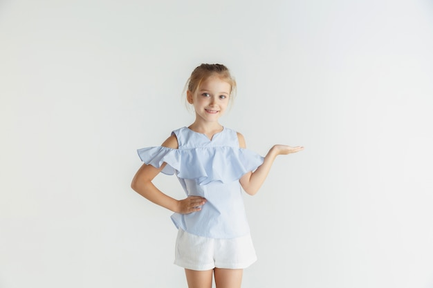 Menina sorridente elegante posando com roupas casuais, isoladas no fundo branco do estúdio. modelo feminino loiro branco. emoções humanas, expressão facial, infância. mostrando o espaço vazio, convidativo
