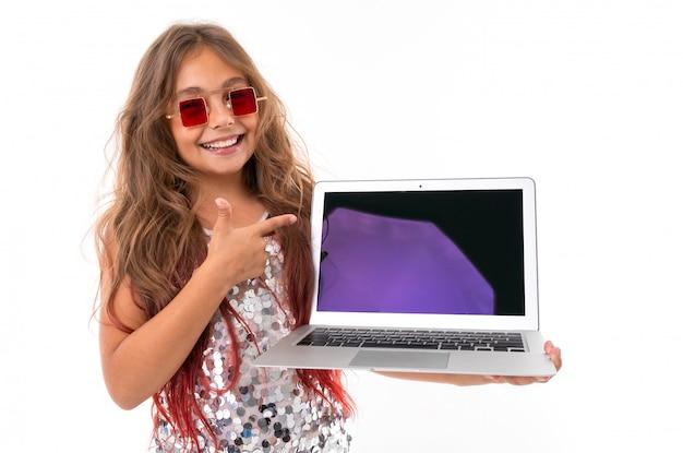 Menina sorridente em óculos de sol quadrados vermelhos segurando laptop moderno com tela preta e apontando para ele isolado