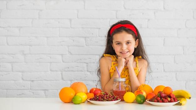 Menina sorridente em pé atrás da mesa branca com frutas maduras orgânicas frescas coloridas