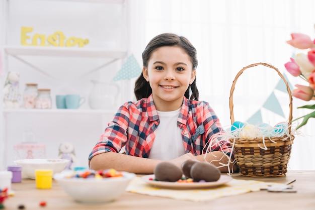 Menina sorridente em pé atrás da mesa com ovos de páscoa de chocolate