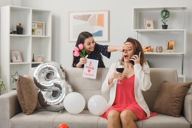 Menina sorridente em pé atrás do sofá segurando um cartão com flores e olhos da mãe cobrindo a mão no feliz dia da mulher na sala de estar