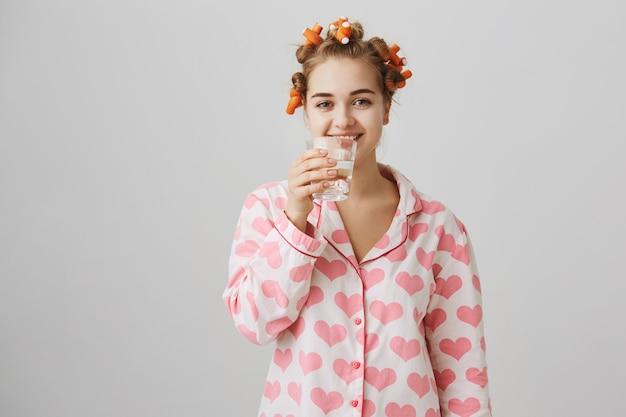 Menina sorridente em pijama bebendo água, usando rolinhos de cabelo