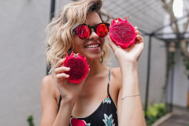 Menina sorridente em pulseira posando com fruta do dragão. foto de uma linda mulher encaracolada em óculos de sol segurando pitaya vermelha.