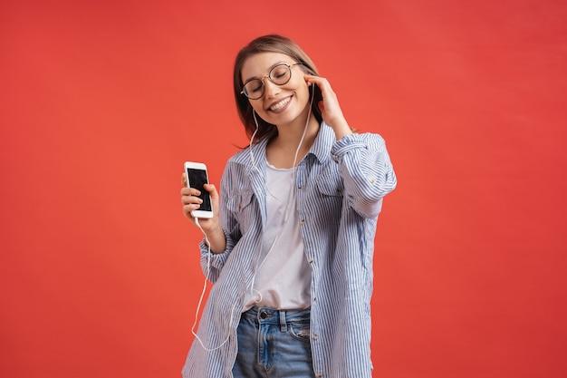 Menina sorridente em roupas casuais e fones de ouvido dançando mãos em movimento.