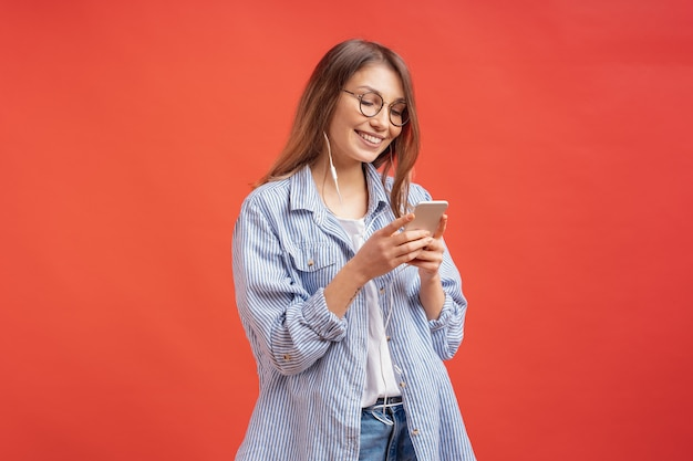 Menina sorridente em roupas casuais e fones de ouvido olhando para a tela do telefone