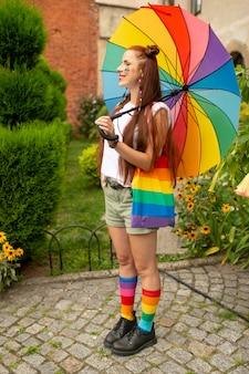 Menina sorridente em roupas coloridas e bandeira lgbt nela posando ao ar livre.