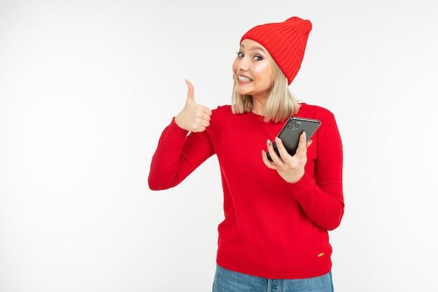 Menina sorridente em roupas vermelhas, navegar na internet em um fundo branco, com espaço de cópia