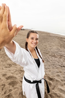 Menina sorridente em traje de arte marcial ao ar livre