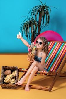 Menina sorridente em traje de banho e óculos de sol, deitado na espreguiçadeira arco-íris com pernas cruzadas e banhos de sol