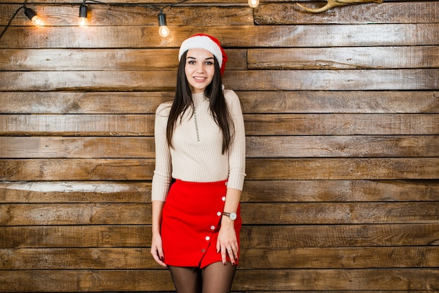 Menina sorridente em um chapéu de papai noel em fundo de madeira