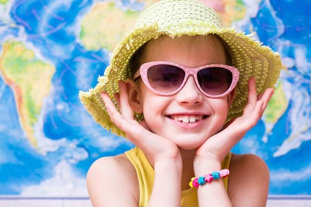 Menina sorridente em um chapéu e óculos de sol pronto para viajar