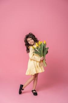 Menina sorridente em um vestido amarelo sobre fundo rosa studio. criança feliz alegre com buquê de flores de tulipas.
