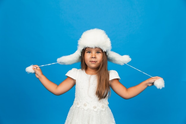 Menina sorridente em um vestido branco e um chapéu de pele branca de inverno se diverte em um fundo azul.