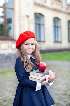 Menina sorridente em uma boina vermelha segura uma pilha de livros com uma maçã perto do prédio da escola.