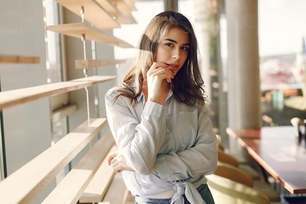 Menina sorridente em uma camisa azul em pé perto da janela
