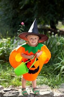 Menina sorridente em uma fantasia de abóbora e com um saco para doces comemora o halloween