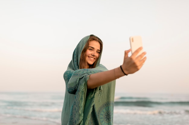 Menina sorridente, embrulhado, em, echarpe, levando, selfie, de, telefone móvel, em, praia