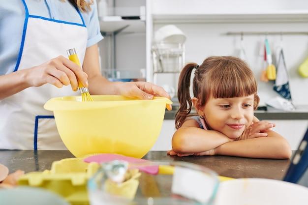 Menina sorridente encostada no balcão da cozinha e assistindo desenho animado no computador tablet quando a mãe dela faz massa de panqueca pela manhã