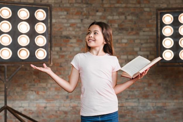 Menina sorridente ensaiando no estúdio segurando um livro aberto