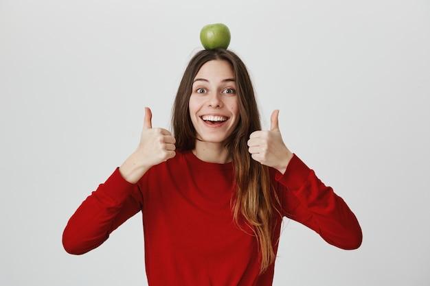 Menina sorridente entusiasta com maçã verde na cabeça mostrando os polegares para cima